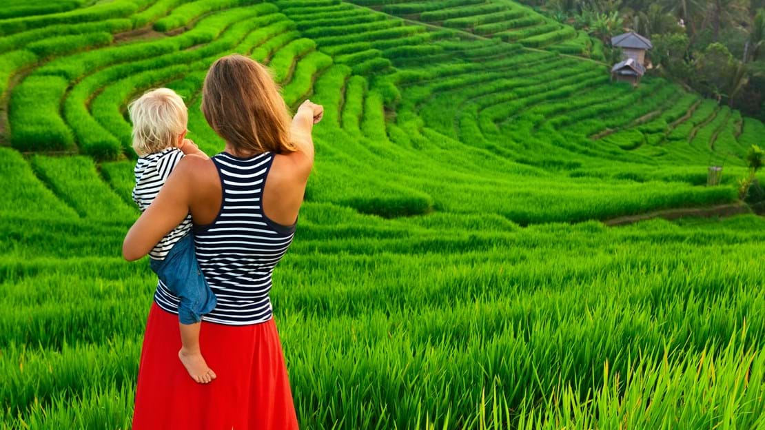 shutterstock_567711667 Beautiful view of Balinese traditional fields. Nature walk in green rice terrace. Happy mother hold happy little baby traveler. Travel adventure with child, family summer vacation in.jpg