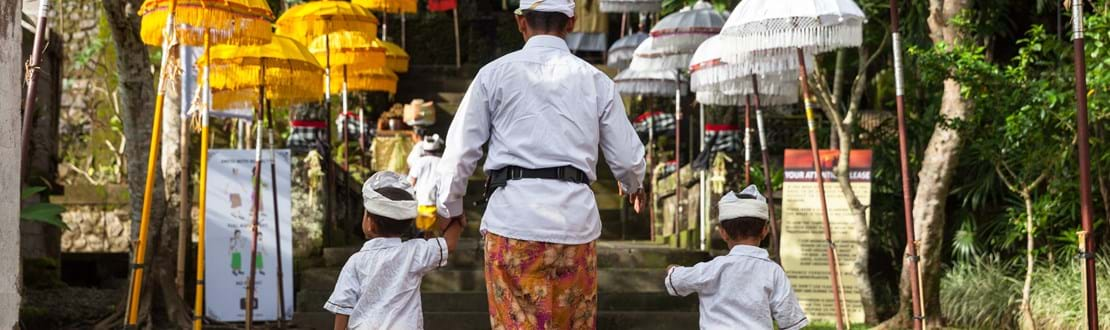 UBUD, INDONESIA - MARCH 2 Man with children walks up the stairs during the celebration before Nyepi (Balinese Day of Silence).jpg