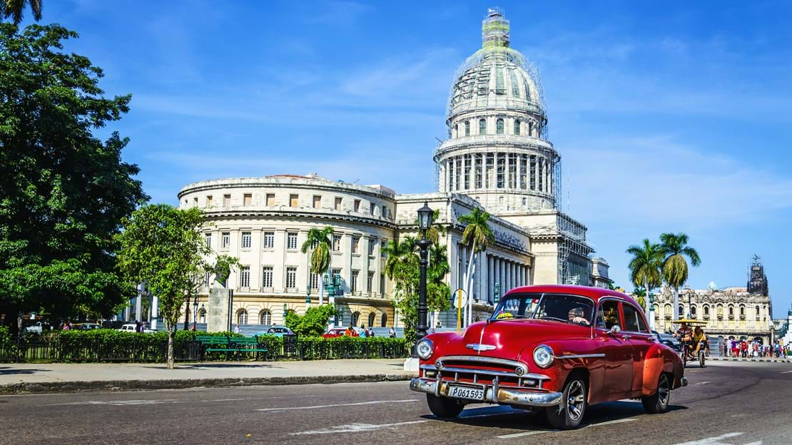 shutterstock_204192301  Old classic American maroon car rides in front of the Capitol.jpg