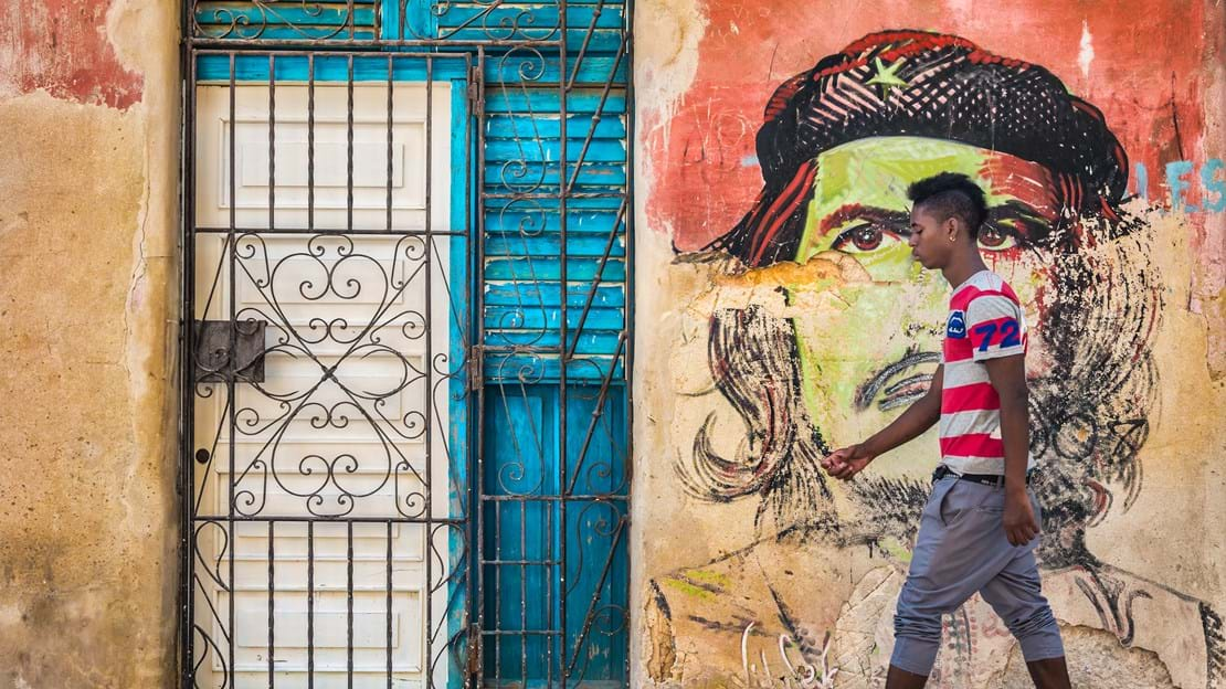 shutterstock_280154453  Young cuban man walks by a colorful Che in Havana.jpg