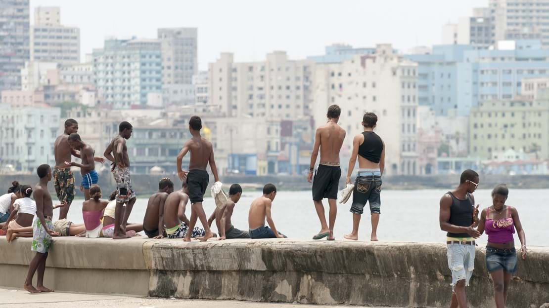 shutterstock_298659509 Group of young Cubans relax on the wall of the Malecon.jpg