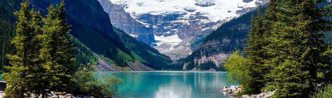 shutterstock_209238454 Beautiful Lake Louise with Victoria Glacier in the background and a glistening emerald lake. Several canoes can be seen..jpg