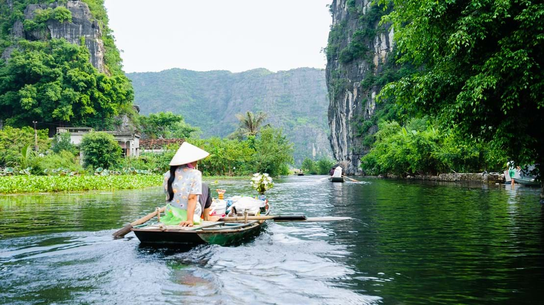 The woman is paddling groceries and fresh flowers boat. Tam Coc Grotto, Ninh Binh Province, Vietnam.jpg